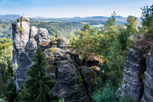 Breathtaking View Of Rocky Cliffs Surrounded By Trees In The Middle Of A Forest