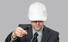 Man In Suit And Dark Glasses Looks From Under The Visor Of White Helmet. He Holds Pen And Draws Attention Or Makes Remark. Isolated On Gray Background