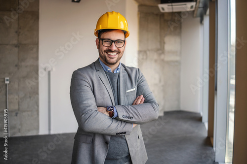 Tablou Canvas Businessman standing in building in construction process with arms crossed and looking at camera