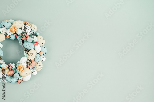 Handmade diy home interior decoration wreath with colorful easter eggs over green background