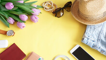 Unisex Travel Flat Lay On Yellow Background With Fresh Violet Tulips Flowers Bouquet, Sunglasses, Stuck Bracelets, Summer Hat, Jeans, Smartphone, Card Holder, Passport, Wireless Headphones And Watch