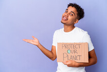Young African American Curly Man Isolated Holding A Protect Our Planet Showing A Copy Space On A Palm And Holding Another Hand On Waist.