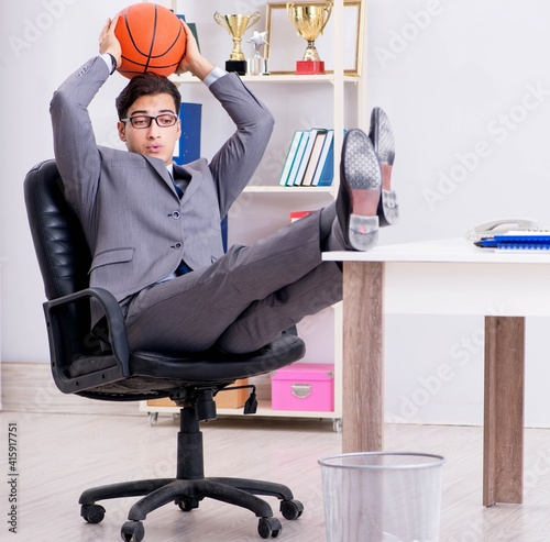 Fototapeta Young businessman playing basketball in office during break obraz