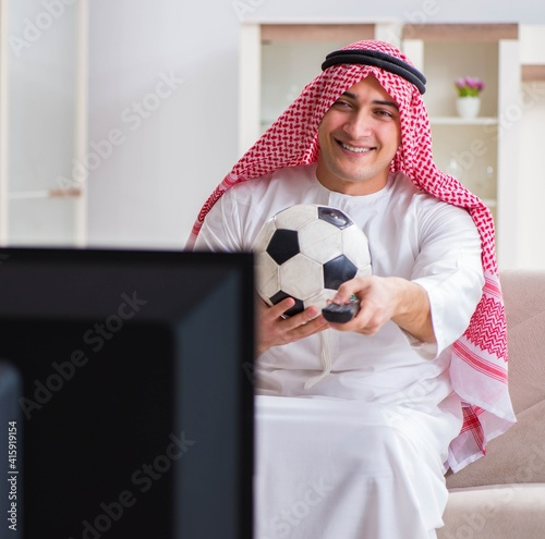 Fototapeta Arab businessman watching tv at home obraz