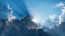 Sun Behind Dark Clouds With Sun Rays On Blue Sky Background