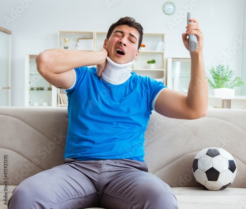 Fototapeta Man with neck injury watching football soccer at home obraz