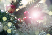 Festive Elegant Christmas Card. Blurry Fir Branches With Holly Berries, Sparkles, Bokeh And Fairy String Lights. Shallow Depth Of Field. Glare Of Christmas Tree Garland On Ball.