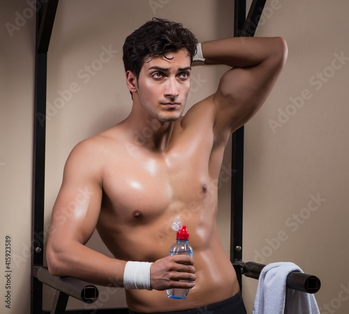 Fototapeta Thirsty man drinking water in sports gym obraz