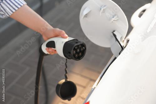 Obraz na plátně Woman inserting plug into electric car socket at charging station, closeup