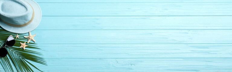 Beach accessories and space for text on light blue wooden background, flat lay. Banner design
