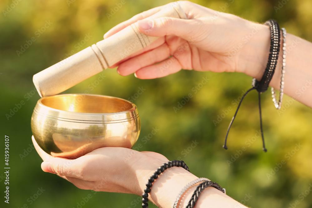 Fototapeta Woman using singing bowl in sound healing therapy outdoors, closeup