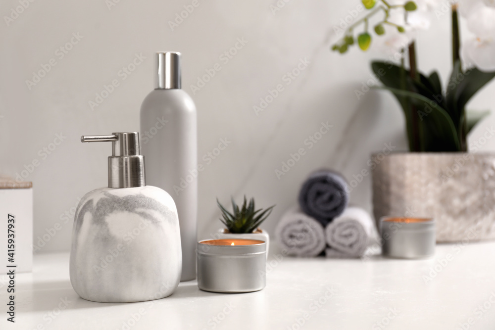 Fototapeta Toiletries and burning candle on countertop in bathroom. Space for text