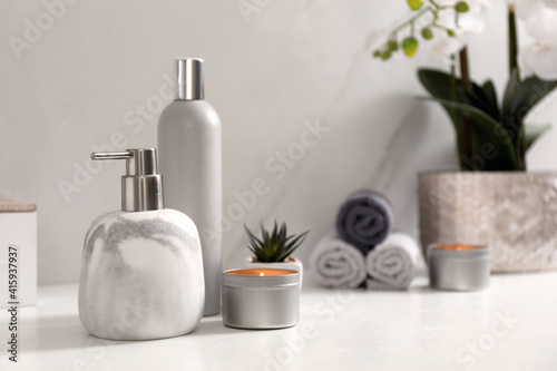 Fototapeta Toiletries and burning candle on countertop in bathroom. Space for text obraz