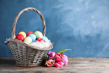 Wicker Basket With Bright Painted Easter Eggs And Spring Flowers On Wooden Table Against Blue Background. Space For Text