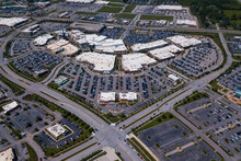 Aerial Drone Photo Of A Busy Shopping Retail Center With Cars In The Parking Lot.
