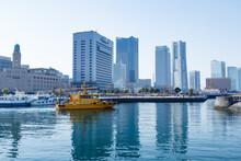 青空を背景に横浜港の桟橋を出航するボートとみなとみらいのビル群