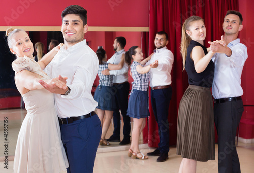Leinwand Poster Cheerful positive people learning to dance waltz in dancing class