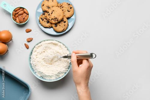 Woman preparing dough on light background