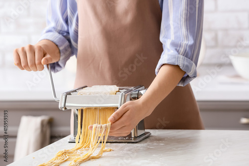 Woman making pasta with machine at table in kitchen