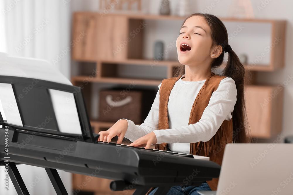 Fototapeta Little girl taking music lessons online at home