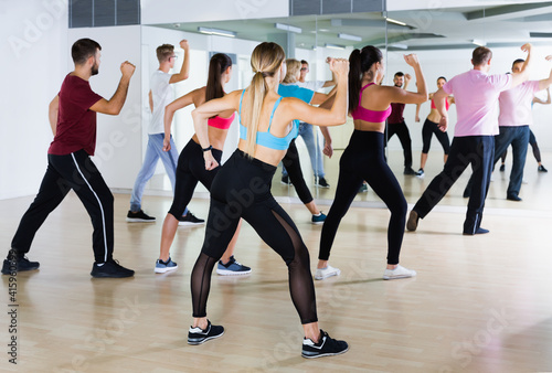 Photo positive men and ladies dancing aerobics at lesson in the dance class