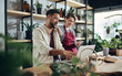Leinwandbild Motiv Shop assistants with laptop working in potted plant store, small business concept.
