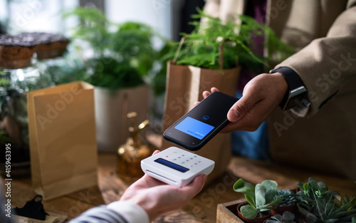 Fotografie, Obraz Customer with smartphone paying in plant store, contactless payment concept