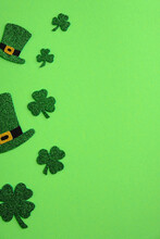 St Patricks Day Frame Of Leprechaun Hats And Shamrock Four Leaves Clover On Green Background. Saint Patrick's Day Vertical Banner Design. Flat Lay, Top View.