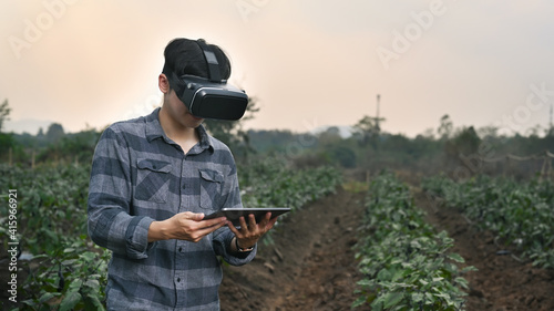 Fototapeta premium Smart farmer man wearing visual reality glasses technology and using digital tablet while standing in agriculture farm.
