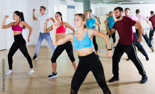 Photo Positive different ages people learning swing steps at dance class and smiling