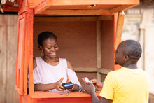 Man Giving His Credit Card To A Woman In A Pos Service Kiosk