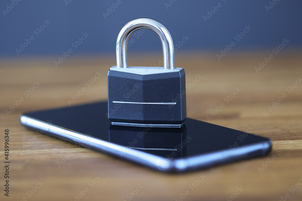 Fototapeta Smartphone with lock on screen is on table