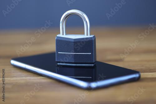 Fototapeta Smartphone with lock on screen is on table obraz