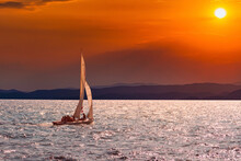Sailboat Sails Over The Sea In On The Background Of A Beautiful Sunset Red Sun. Sea On The Horizon Rests On The Mountains. Beautiful Sunset On The Background Of Mountains