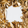White card note with frame of golden leaves. Top view of frame made of golden colored leafs with square paper note in the middle with copy space for text or product