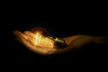 Incandescent Light Bulb In A Hand On Black Background