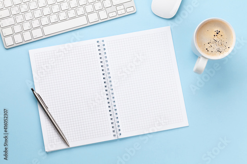 Fototapeta Office desk with supplies, coffee and blank notepad