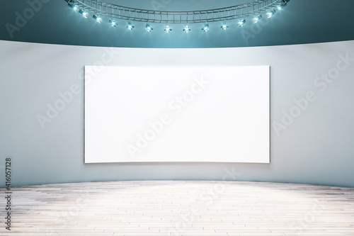 Fototapeta Spacious empty hall room with blank white poster on light wall, parquet floor and led light on top. Mockup obraz