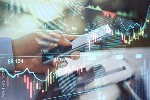 Obraz Online trading business concept with man hand using smartphone and transparent digital display with stock market graphs and diagram - fototapety do salonu