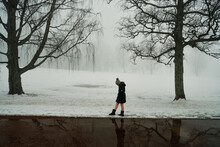 In The Misty Morning. It's Dark And Grey Outside. The Young Girl Is Walking And Wonder Over The Great Nature. Moody And Dramatic Scenery.