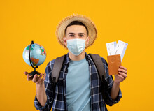 Young Tourist In Protective Mask Holding Globe, Passport And Plane Tickets, Looking At Camera On Orange Background