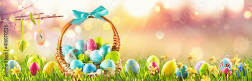 Easter Eggs in a Basket on Green Grass Sunny Background