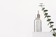 Natural Skin Care Products Concept. Herbal Mineral Cosmetics, Serum, Hyaluronic Acid On White Podium. Transparent Dark Glass Bottle With Dropper, Copy Space
