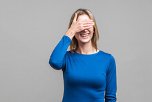 So Shameful, I'd Rather Not Watch This! Portrait Of Bashful Positive Woman In Elegant Blue Dress Covering Eyes With Hand And Laughing, Shy To Look. Indoor Studio Shot Isolated On Gray Background