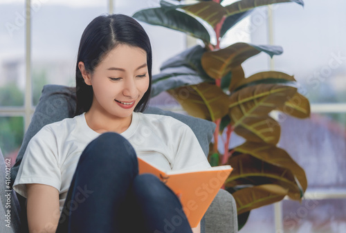 Canvas Print Asian woman reading orange book with smile on a sofa at home