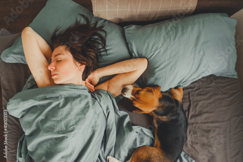 Beautiful young girl sleeps in the morning in bed with her pet. Fototapet