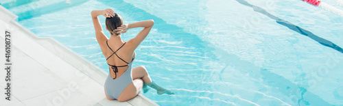 Fototapeta back view of woman in swimsuit adjusting hair while sitting near swimming pool in spa center, banner obraz