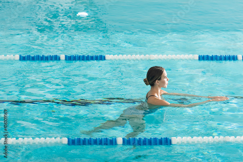 Fototapeta Side view of young woman relaxing in swimming pool obraz