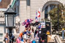 People Walking On Street With Union Jack Flag Umbrella And Closeup Of Lantern In United Kingdom Bokeh Background