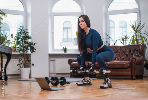 Fototapeta Strong girl with barbell and laptop works out in cosy and modern apartment with furniture. obraz